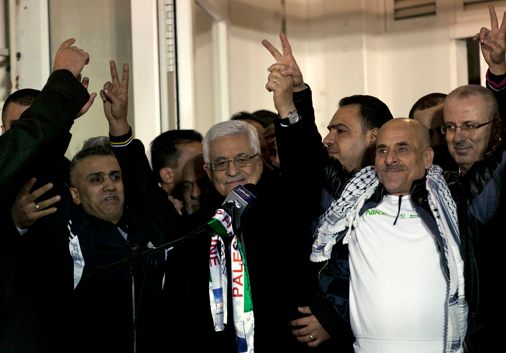 . Palestinian President Mahmoud Abbas, center, receives released Palestinian prisoners during a welcome ceremony after their arrival at the Palestinian headquarters in the West Bank city of Ramallah, Tuesday, Dec. 31, 2013. Israel released more than two dozen Palestinian prisoners convicted in deadly attacks against Israelis early Tuesday as part of a U.S.-brokered package to restart Mideast peace talks. (AP Photo/Nasser Nasser)