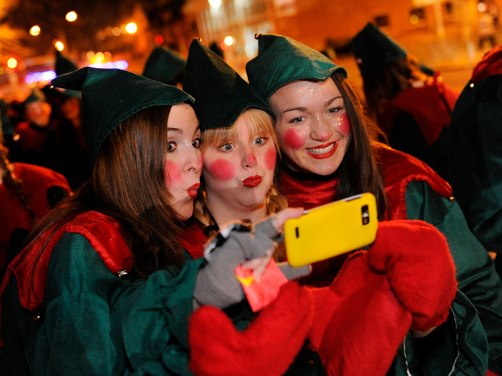 . Smoky Hill High School students Kaitlin Gibson, left, Jessica Schnitzer, center, and Danielle Pukansty, right, photographed themselves in elf costumes before the parade. The annual Parade of Lights filed past the illuminated City and County building in downtown Denver Friday night, November 30. 2012. The parade with 11 floats, 7 bands, 5 giant balloons and more lights than anyone could count, had enough holiday spirit for everyone. Karl Gehring/ The Denver Post