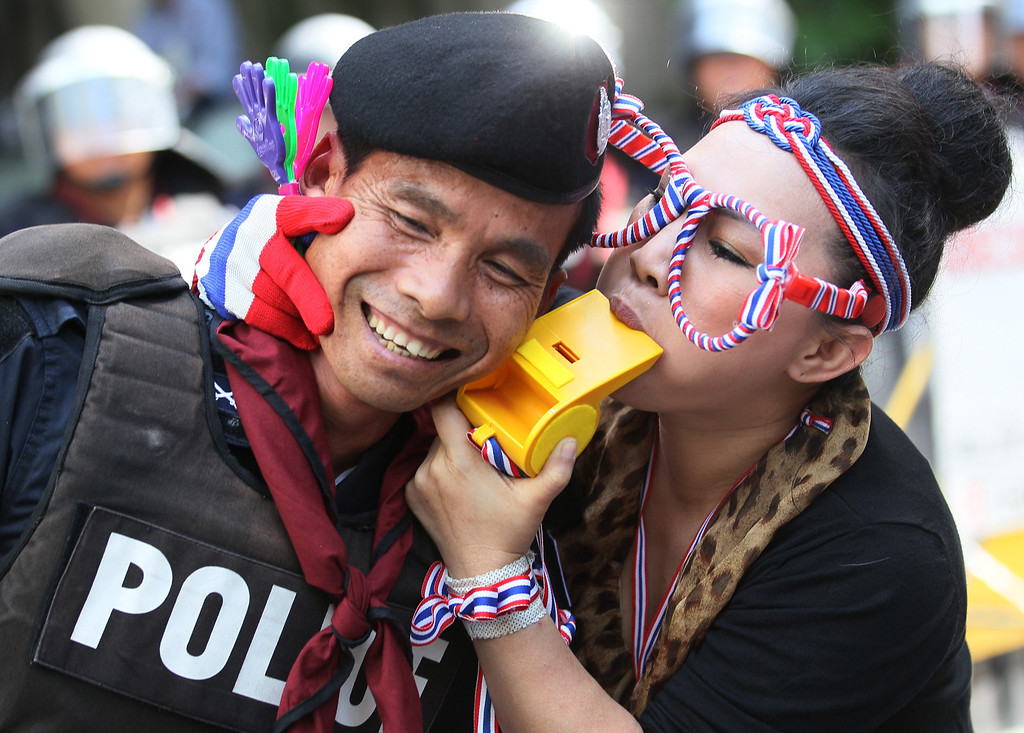 . An anti-government protester blows a giant whistle to a riot police officer outside the headquarters of Prime Minister Yingluck Shinawatra\'s ruling Pheu Thai Party in Bangkok, Thailand, Friday, Nov. 29, 2013. The protesters staged a rally in a bid to topple Yingluck outside the party headquarters where hundreds of riot police stood guard to prevent them from entering. (AP Photo/Sakchai Lalit)
