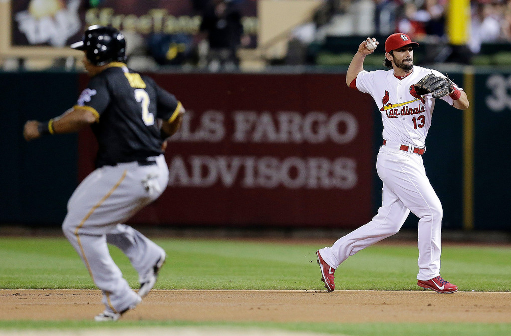 . St. Louis Cardinals second baseman Matt Carpenter (13) throws to first base to complete a double play before Pittsburgh Pirates\' Marlon Byrd (2) can get back to the base in the second inning of Game 5 of a National League baseball division series, Wednesday, Oct. 9, 2013, in St. Louis. Pedro Alvarez lined out to Carpenter and Byrd was caught off base for the second out. (AP Photo/Charlie Riedel)