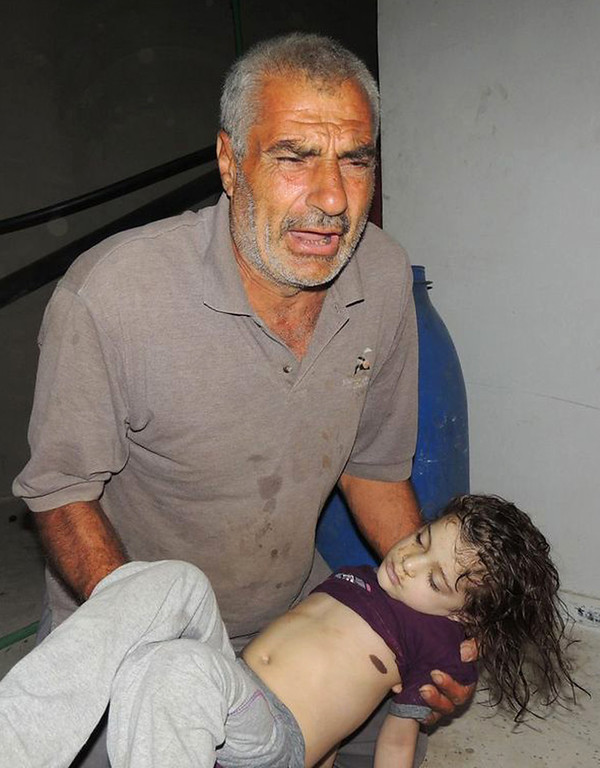 . This citizen journalism image provided by the Local Committee of Arbeen which has been authenticated based on its contents and other AP reporting, shows a Syrian man reacts as he carries a dead body of a Syrian girl, after an alleged poisonous gas attack fired by regime forces, according to activists in Arbeen town, Damascus, Syria, Wednesday, Aug. 21, 2013. (AP Photo/Local Committee of Arbeen)