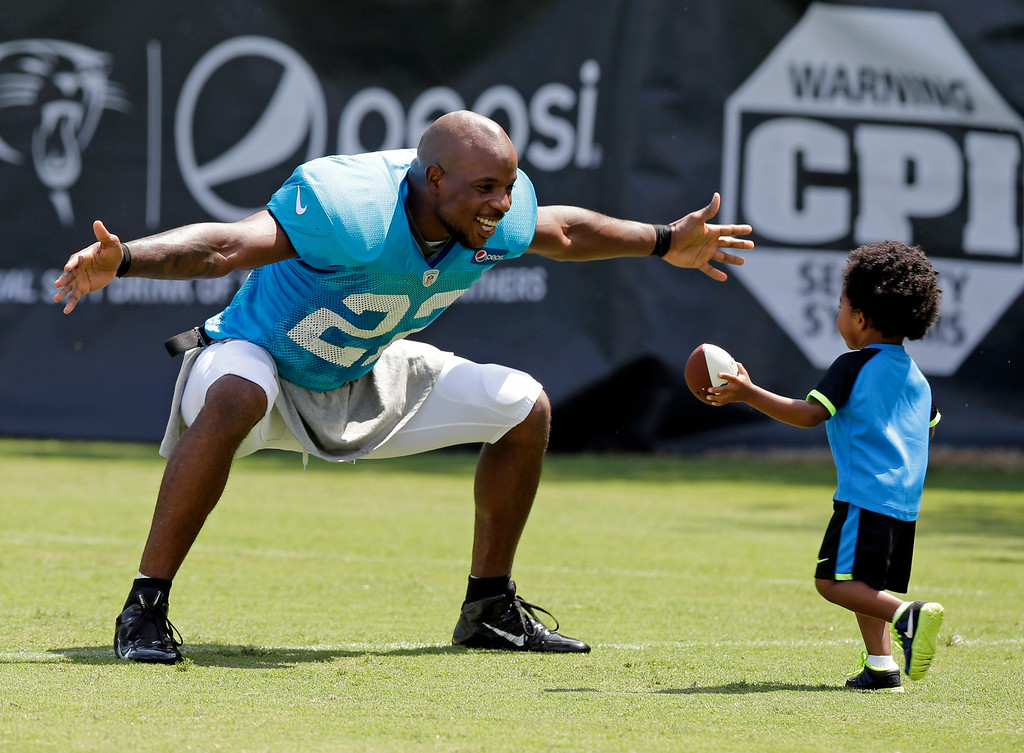 . Carolina Panthers\' Josh Thomas, left, reaches out to hug his son, Dallas, 2, right, after an NFL football practice at their training camp in Spartanburg, S.C., Tuesday, July 29, 2014. (AP Photo/Chuck Burton)