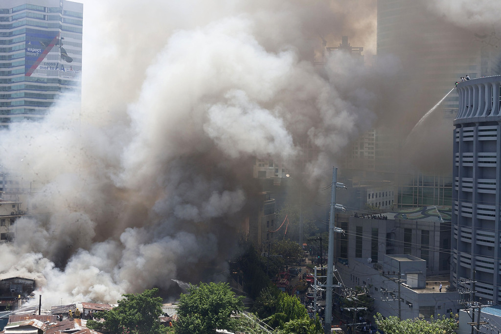 . Smoke rises after a fire engulfed a shanty town in the financial district of Manila on July 11, 2013. There were no immediate reports of casualties from the blaze, which occurred mid-morning amid government plans to relocate thousands of families living in areas vulnerable to floods and typhoons. KARL MALAKUNAS/AFP/Getty Images