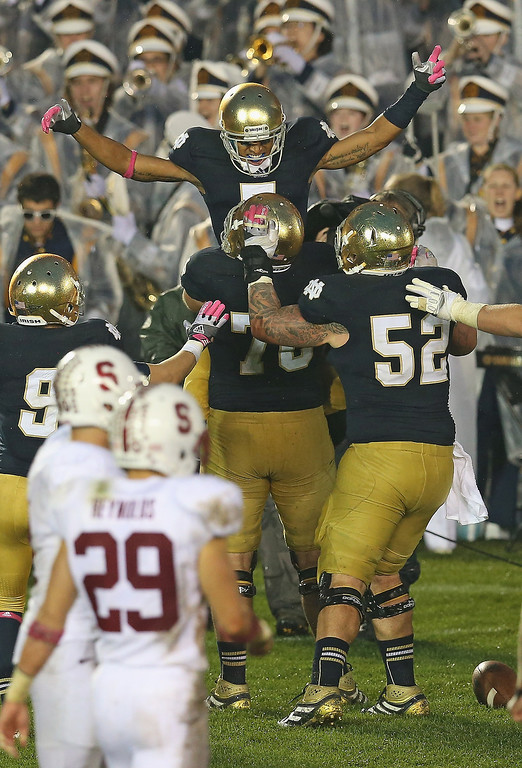 . T.J. Jones #7 of the Notre Dame Fighting Irish celebrates catching the game-winning touchdown pass in overtime against the Standford Cardinal with teammates including Zack Martin #70 at Notre Dame Stadium on October 13, 2012 in South Bend, Indiana. Notre Dame defeated Stanford 20-13 in overtime.  (Photo by Jonathan Daniel/Getty Images)