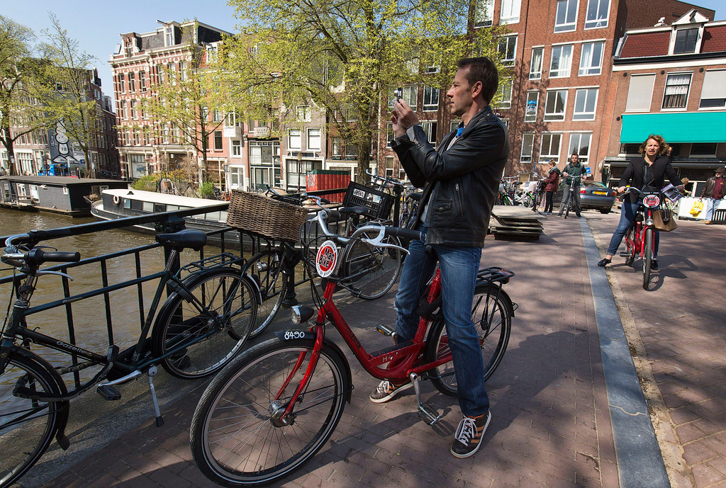 . A man riding a rental bike takes a picture of houseboats at the Prinsengracht canal in Amsterdam April 24, 2013. The Royal celebrations in the Netherlands this week put the country and the capital Amsterdam on front pages and television screens around the world with an orange splash. There\'s plenty to see and do in 48 hours in this compact city, where the world-famous Rijksmuseum only recently reopened after an extensive renovation. Picture taken April 24, 2013. REUTERS/Michael Kooren