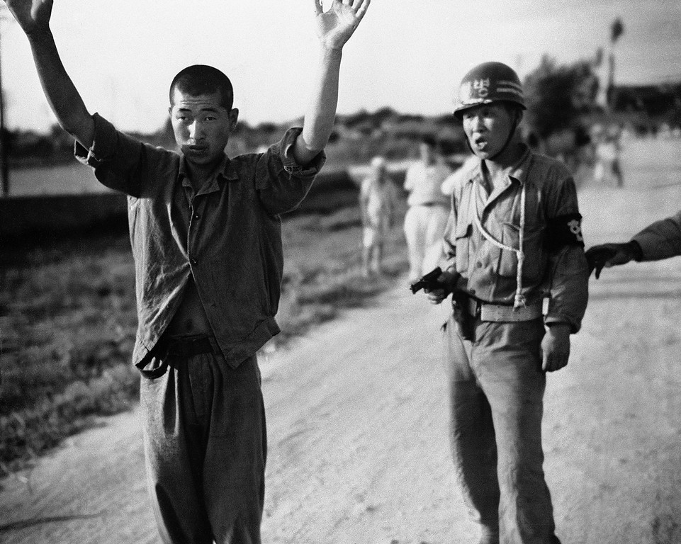 . A South Korean military policeman marches a North Korean prisoner of war to a stockade somewhere in South Korea on July 21, 1950. (AP Photo)