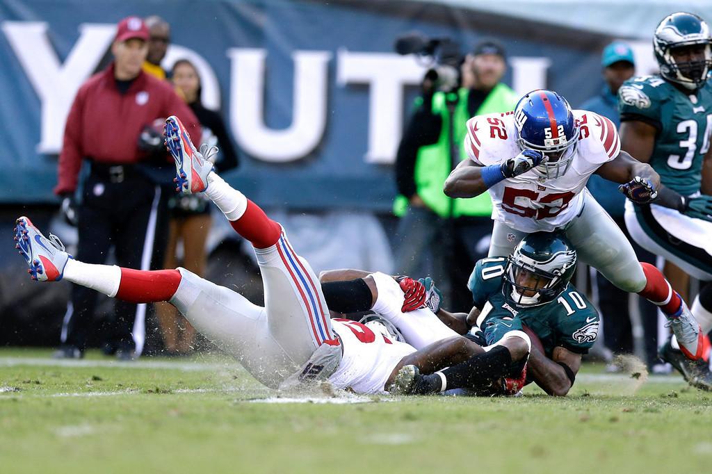 . Philadelphia Eagles\' DeSean Jackson (10) is tackled by New York Giants\' Jon Beason (52) during the second half of an NFL football game Sunday, Oct. 27, 2013 in Philadelphia. (AP Photo/Matt Rourke)