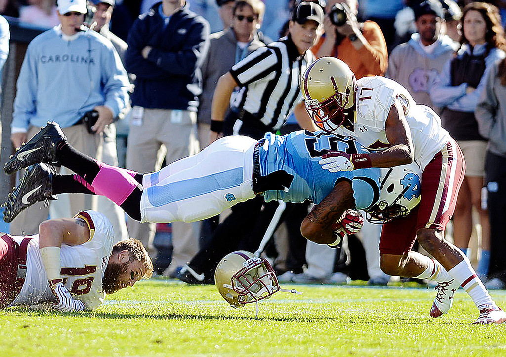 . North Carolna\'s A.J. Blue goes airborne for a first down as Boston College\'s Bryce Jones (17) and Sean Sylvia (19) make the stop during an NCAA college football game Saturday, Oct. 26, 2013, in Chapel Hill, N.C. (AP Photo/The Herald-Sun, Bernard Thomas)