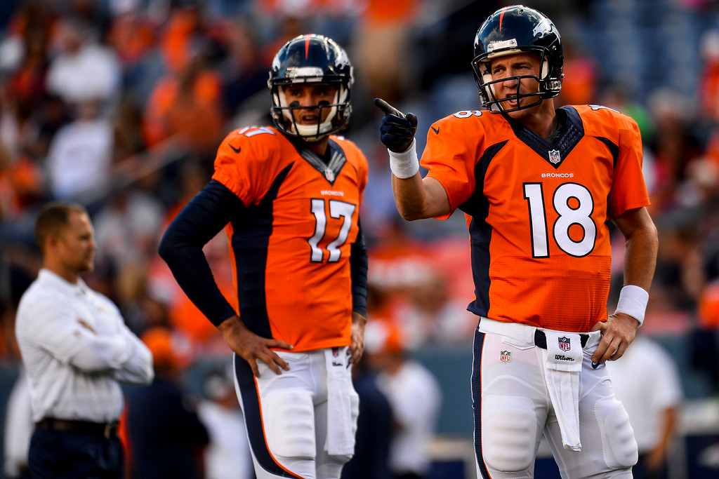 . DENVER, CO - AUGUST 23:  Peyton Manning (18) and Brock Osweiler (17) of the Denver Broncos warm up before the start of a preseason football game at Sports Authority Field at Mile High on Saturday, August 23, 2014 in Denver, Colorado.  (Photo by Steve Nehf/The Denver Post)