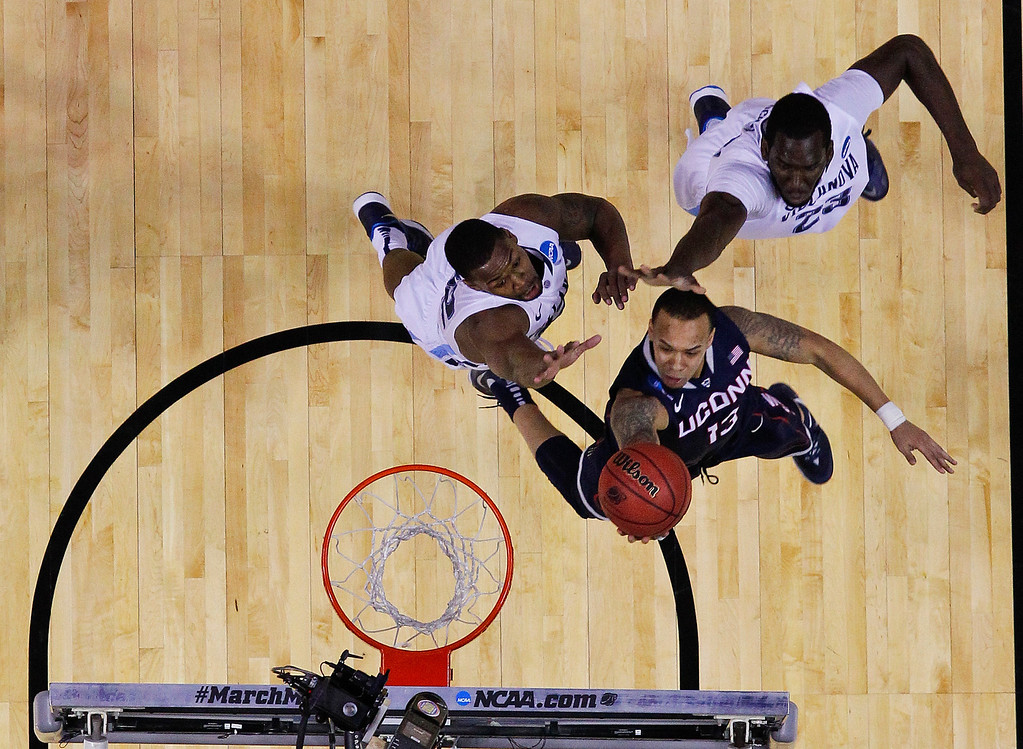 . Connecticut\'s Shabazz Napier drives past Villanova\'s JayVaughn Pinkston, left, and Daniel Ochefu (23) during the first half of a third-round game in the NCAA men\'s college basketball tournament in Buffalo, N.Y., Saturday, March 22, 2014. (AP Photo/Bill Wippert)