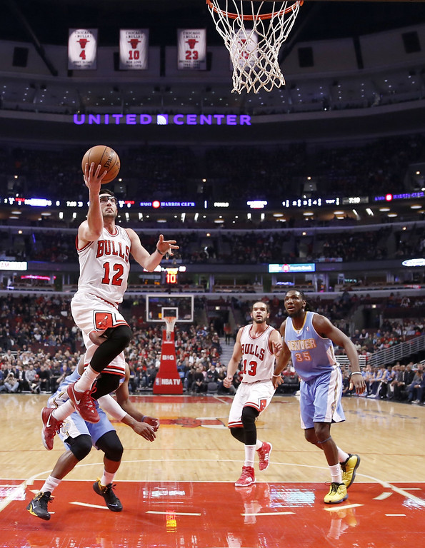 . Chicago Bulls guard Kirk Hinrich (12) scores past Denver Nuggets guard Randy Foye as Joakim Noah (13) and Denver Nuggets forward Kenneth Faried (35) watch during the first half of an NBA basketball game Friday, Feb. 21, 2014, in Chicago. (AP Photo/Charles Rex Arbogast)