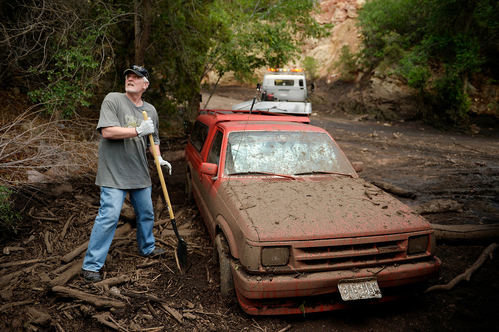 . Manitou Springs, CO. - July 02: Ken Cisek looks to the darkening sky as he digs out his truck after being caught in his one level home in the path of a flash flood that washed through houses, streets and businesses when a downpour hit the Waldo Canyon burn scar in El Paso County July 02, 2013 Manitou Springs, Colorado. (Photo By Joe Amon/The Denver Post)