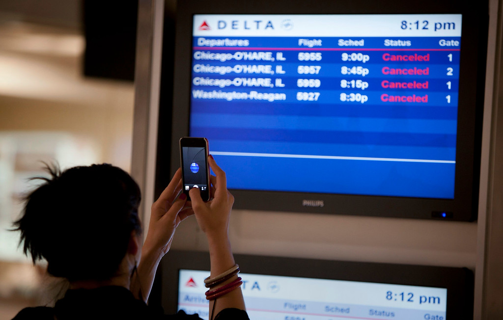 . A woman takes a photo with her phone of a screen that displays information on cancelled flights after a Southwest Airlines Boeing 737 made an emergency landing at LaGuardia airport in New York July 22, 2013. Several people were injured when the Southwest Airlines Flight 345 with 150 people on board landed at LaGuardia Airport without its nose gear, officials said.   REUTERS/Carlo Allegri