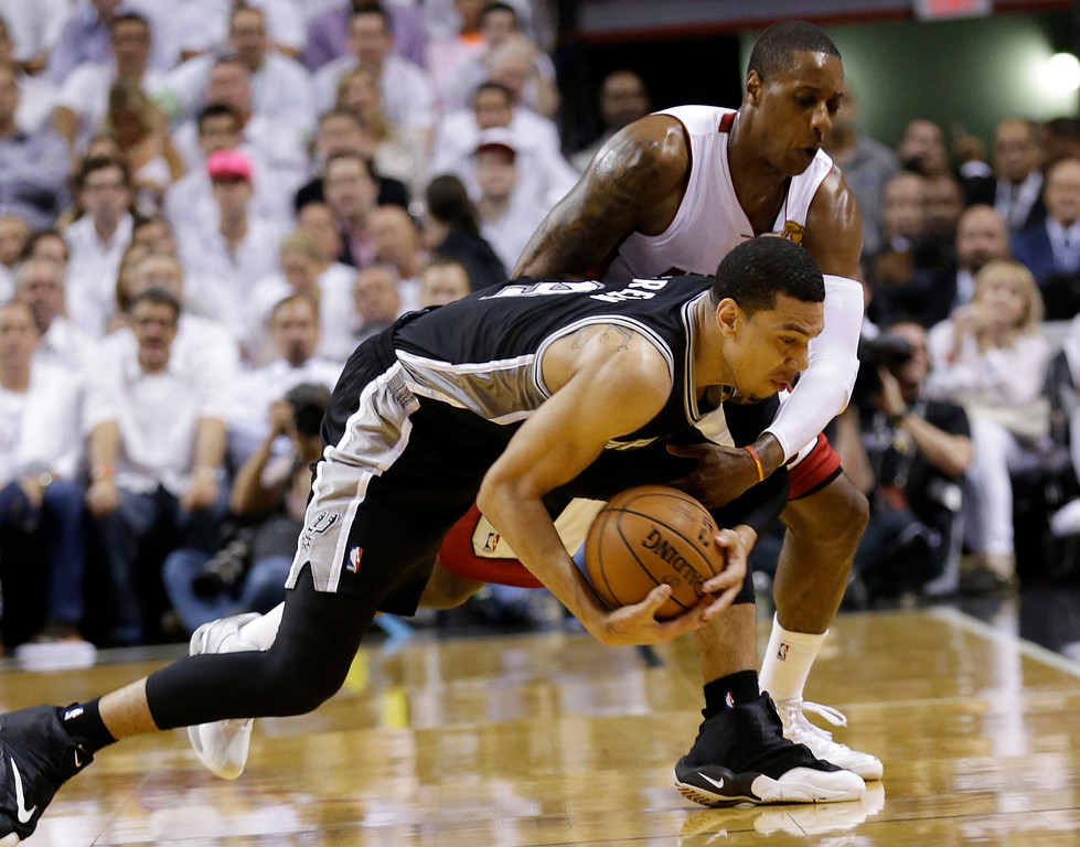 . San Antonio Spurs guard Danny Green (4) and Miami Heat guard Mario Chalmers (15), go after a loose ball during the first half in Game 3 of the NBA basketball finals, Tuesday, June 10, 2014, in Miami. (AP Photo/Wilfredo Lee)
