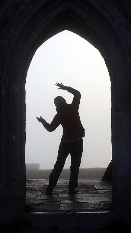 . A visitor to Glastonbury Tor welcomes the sun rise as she stands inside St. Michael\'s Tower, a ruined 14th-century church tower, as the rising sun begins to clear the early morning mist and fog near the town of Glastonbury on September 4, 2013 in Somerset, England.  (Photo by Matt Cardy/Getty Images)