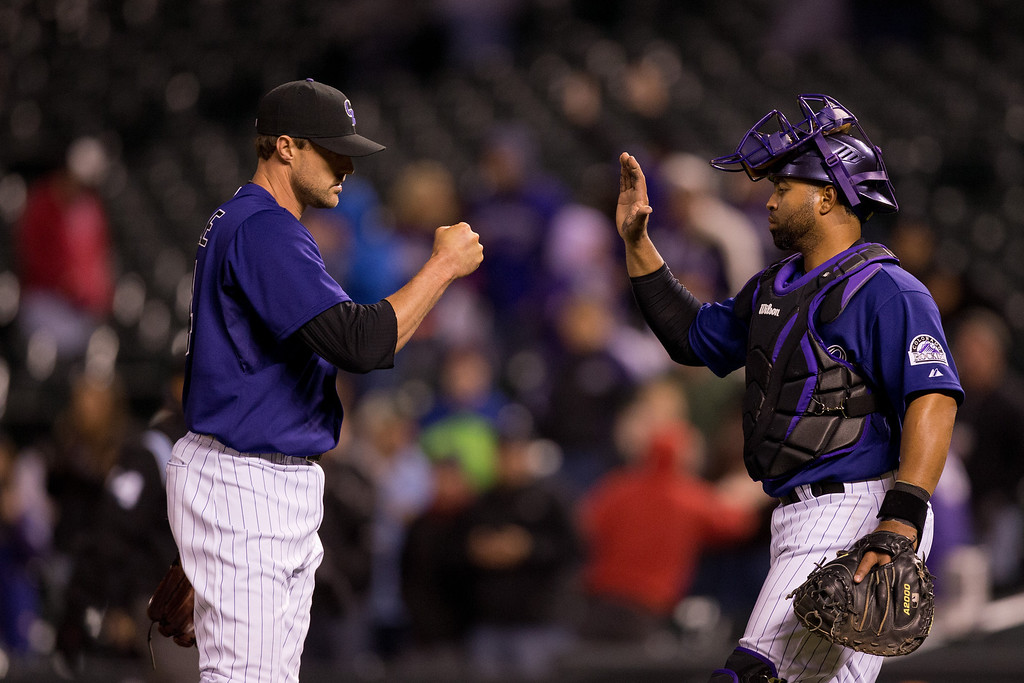 . Relief pitcher Matt Belisle #34 of the Colorado Rockies celebrates with catcher Wilin Rosario #20 after defeating the Chicago White Sox 8-1 at Coors Field on April 7, 2014 in Denver, Colorado. (Photo by Justin Edmonds/Getty Images)