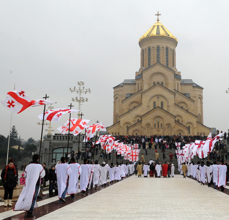 . A procession of Georgian believers arrives at the Tbilisi cathedral on January 7, 2013 during the Christmas celebrations. Orthodox Christians celebrate Christmas on January 7 in the Middle East, Russia and other Orthodox churches that use the old Julian calendar instead of the 17th-century Gregorian calendar adopted by Catholics, Protestants, Greek Orthodox and commonly used in secular life around the world.   AFP PHOTO / VANO  SHLAMOV/AFP/Getty Images
