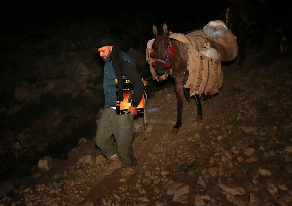 . In this picture taken early Sunday, April 20, 2014, Ibrahim Abdulghani, 32, leads his horse with the belongings of Syrian refugees as he descends from the 2,814-meter (9,232-foot) high Mount Hermon (Jabal el-Sheikh), in southeast Lebanon. Abdulghani, from Syria, works as a construction worker during the day in Lebanon and volunteers at night to help Syrians escape. (AP Photo/Hussein Malla)