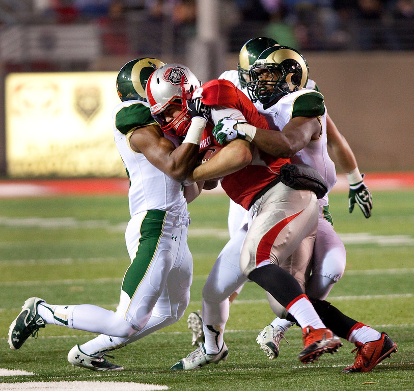. New Mexico\'s Cole Gautsche (8) is tackled by the Colorado State defense in the first half of an NCAA college football game on Saturday, Nov. 16, 2013 in Albuquerque, N.M. (AP Photo/Eric Draper)