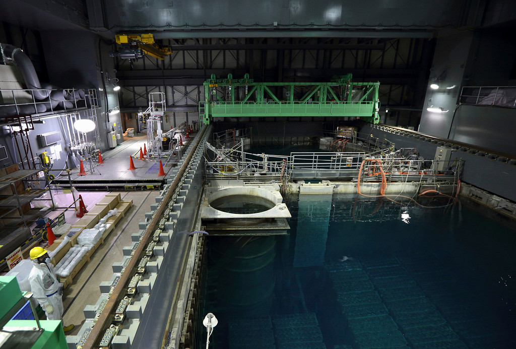 . A Tokyo Electric Power Co. employee wearing a protective suit and a mask stands next to the spent fuel pool inside the building housing the Unit 4 reactor at the Fukushima Dai-ichi nuclear power plant in Okuma, Fukushima Prefecture, Japan, Thursday, Nov. 7, 2013. (AP Photo/Tomohiro Ohsumi, Pool)