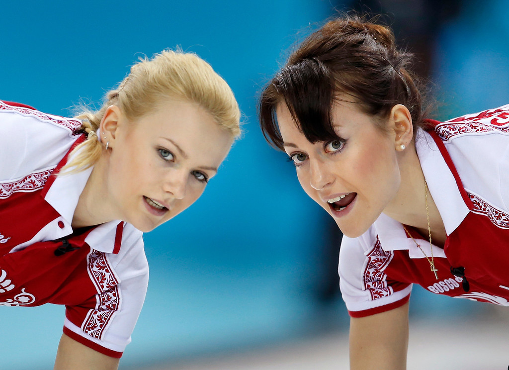 . Russiaís Alexandra Saitova, left, and Ekaterina Galkina look to the house while sweeping ahead of the rock during women\'s curling competition against Britain at the 2014 Winter Olympics, Monday, Feb. 17, 2014, in Sochi, Russia. (AP Photo/Robert F. Bukaty)