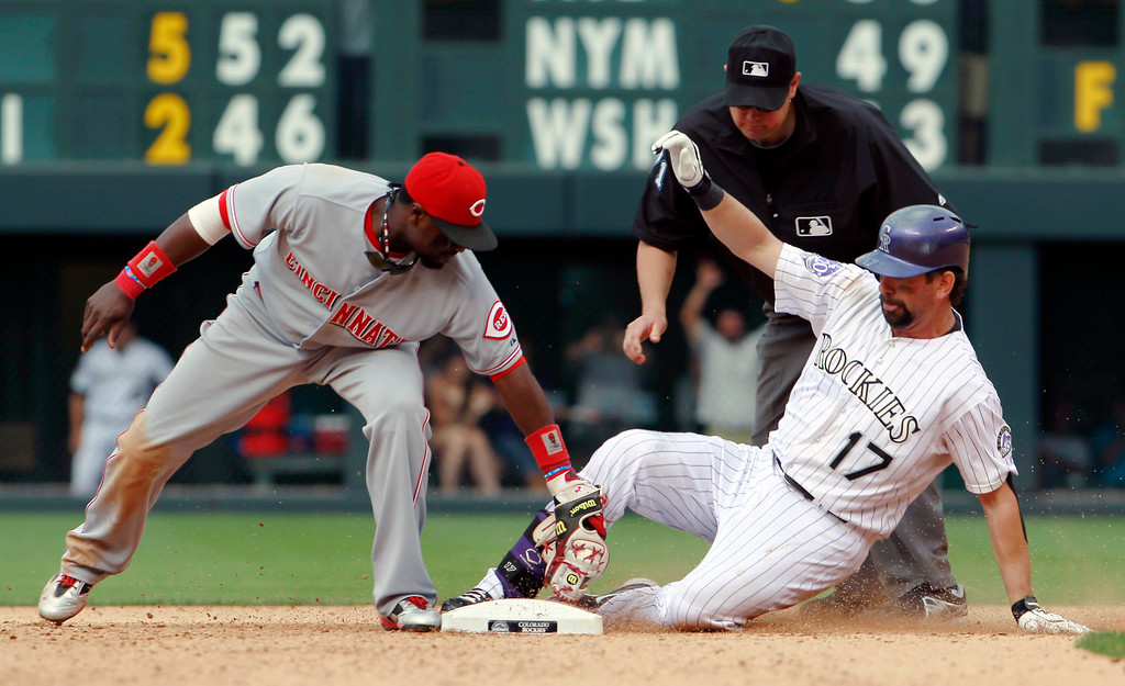 . Colorado Rockies\' Todd Helton, right, slides safely into second base with a double as Cincinnati Reds second baseman Brandon Phillips, left, turns to apply the tag under the watch of second base umpire Jordan Baker in the seventh inning of a baseball game in Denver on Sunday, Sept. 1, 2013. The hit was the 2,500th in Helton\'s career. (AP Photo/David Zalubowski)