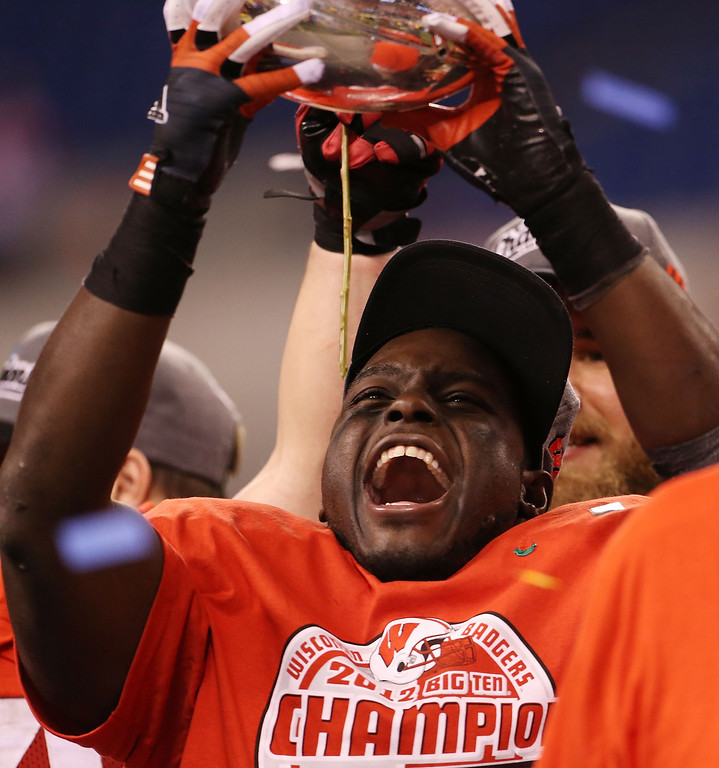 . INDIANAPOLIS, IN - DECEMBER 01: Montee Ball #28 of the Wisconsin Badgers celebrates the Big Ten Championship holding the Amos Alonzo Stagg Championship Trophy after defeating the Nebraska Cornhuskers 70-31 at Lucas Oil Stadium on December 1, 2012 in Indianapolis, Indiana.  (Photo by Leon Halip/Getty Images)