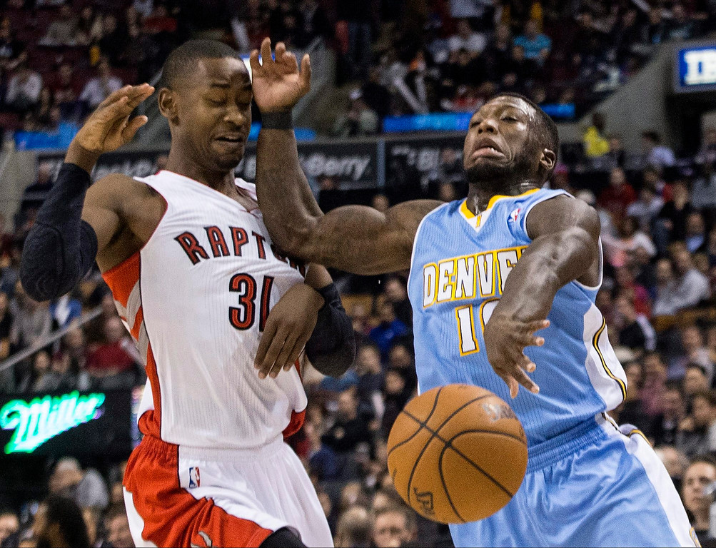 . Toronto Raptors\' Terrence Ross, left, fouls Denver Nuggets\' Nate Robinson during the first half of an NBA basketball game on Sunday, Dec. 1, 2013, in Toronto. (AP Photo/The Canadian Press, Chris Young)