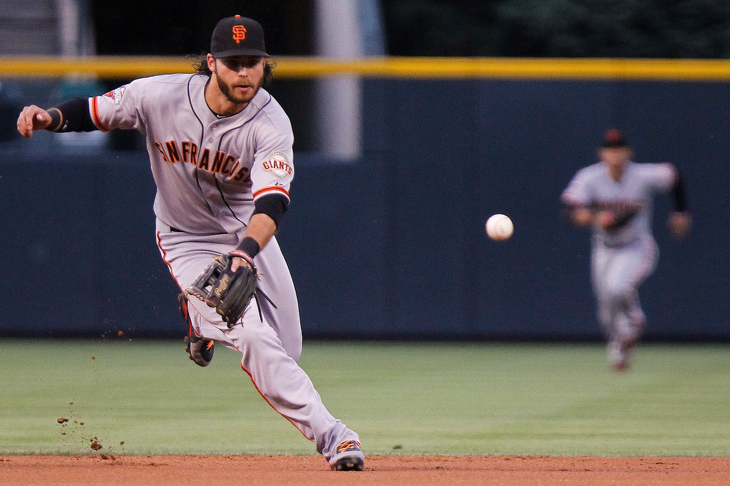 . San Francisco Giants\' Brandon Crawford grabs a ground ball by Colorado Rockies\' Troy Tulowitzki during the first inning of a baseball game, Wednesday, Aug. 28, 2013, in Denver. (AP Photo/Barry Gutierrez)
