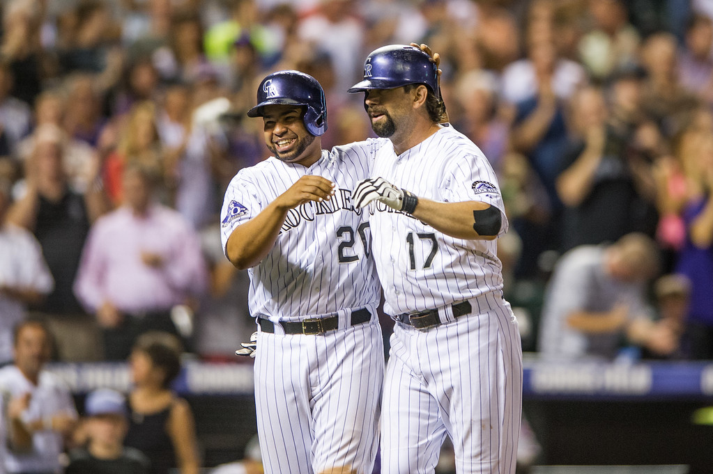 . DENVER, CO - AUGUST 30:  Todd Helton #17 of the Colorado Rockies celebrates his second three-run home run of the game for his 2,499th career hit with teammateWilin Rosario #20 in the seventh inning of a game against the Cincinnati Reds at Coors Field on August 30, 2013 in Denver, Colorado. The Rockies beat the Reds 9-6. (Photo by Dustin Bradford/Getty Images)