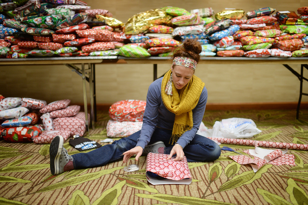 """. DENVER, CO. DECEMBER 21: Jamie McCleary of Denver is wrapping Christmas gift during the annual Father Woody Christmas Party in Denver, Colorado December 21, 2013. In advance of handing out 5,000 gifts, volunteers are doing a \""""wrapping party\"""" at the Sheraton Denver Downtown Hotel. (Photo by Hyoung Chang/The Denver Post)"""