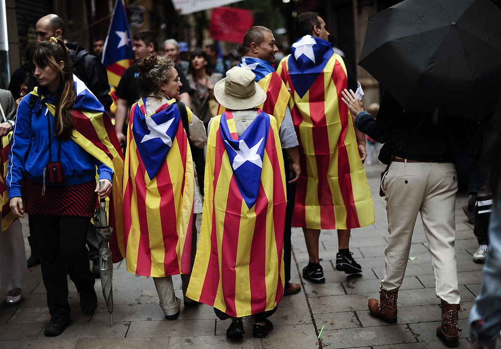 """. People walk wrapped in Catalonia\'s flag \""""Estelada\"""" during celebrations for Catalonia National Day, or Diada, in Barcelona on September 11, 2013. Independence-seeking Catalans marshalled their forces today in a bid to create a 400-kilometre (250-mile) human chain they say will stretch across 86 cities, towns and villages along the coast of the northeastern region on the Mediterranean, passing landmarks such as the Sagrada Familia basilica in Barcelona and the city\'s Camp Nou football stadium. JOSEP LAGO/AFP/Getty Images"""