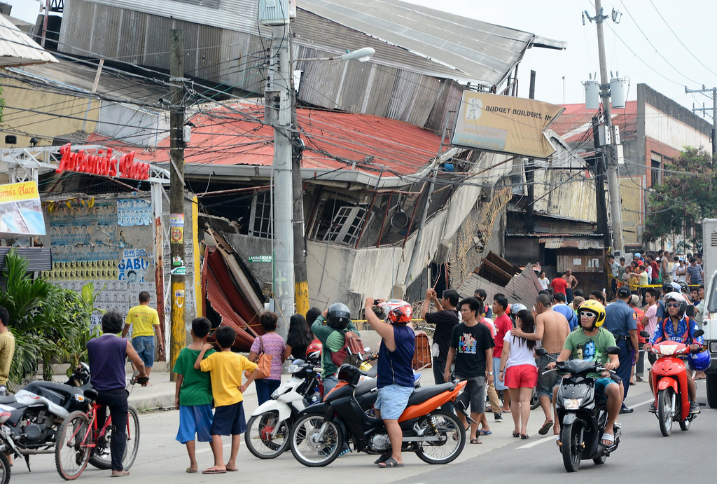 . People gather on the street next to damaged buildings in Cebu City, Philippines after a major 7.1 magnitude earthquake struck the region on October 15, 2013. AFP PHOTOSTR/AFP/Getty Images