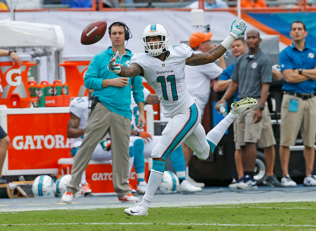 . Mike Wallace #11 is unable to catch the ball thrown by Ryan Tannehill #17 (not pictured) of the Miami Dolphins during second quarter action against the New York Jets on December 29, 2013 at Sun Life Stadium in Miami Gardens, Florida. (Photo by Joel Auerbach/Getty Images)