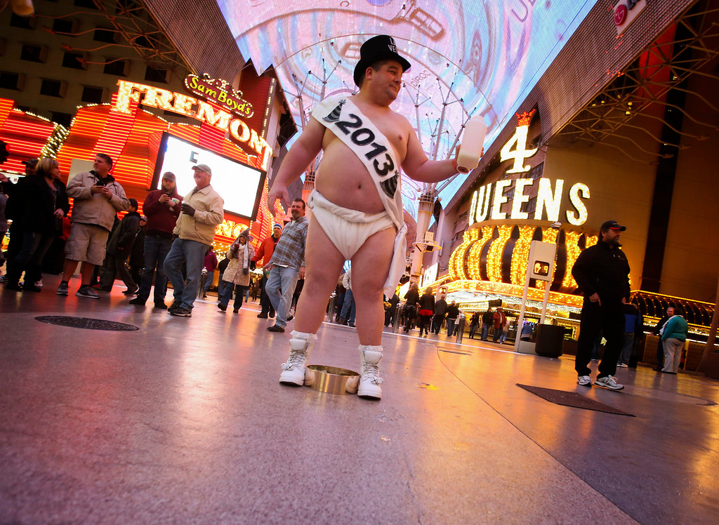 """. Ronnie \""""Tank\"""" Campbell of Fayetteville, N.C.  portrays Baby New Year on the Fremont Street Experience in Las Vegas, Monday, Dec. 31, 2012. \""""This is what keeps me warm,\"""" said the 315 lb. truck driver, referring to his pi�a colada. (AP Photo/Las Vegas Review-Journal, Jeff Scheid)"""