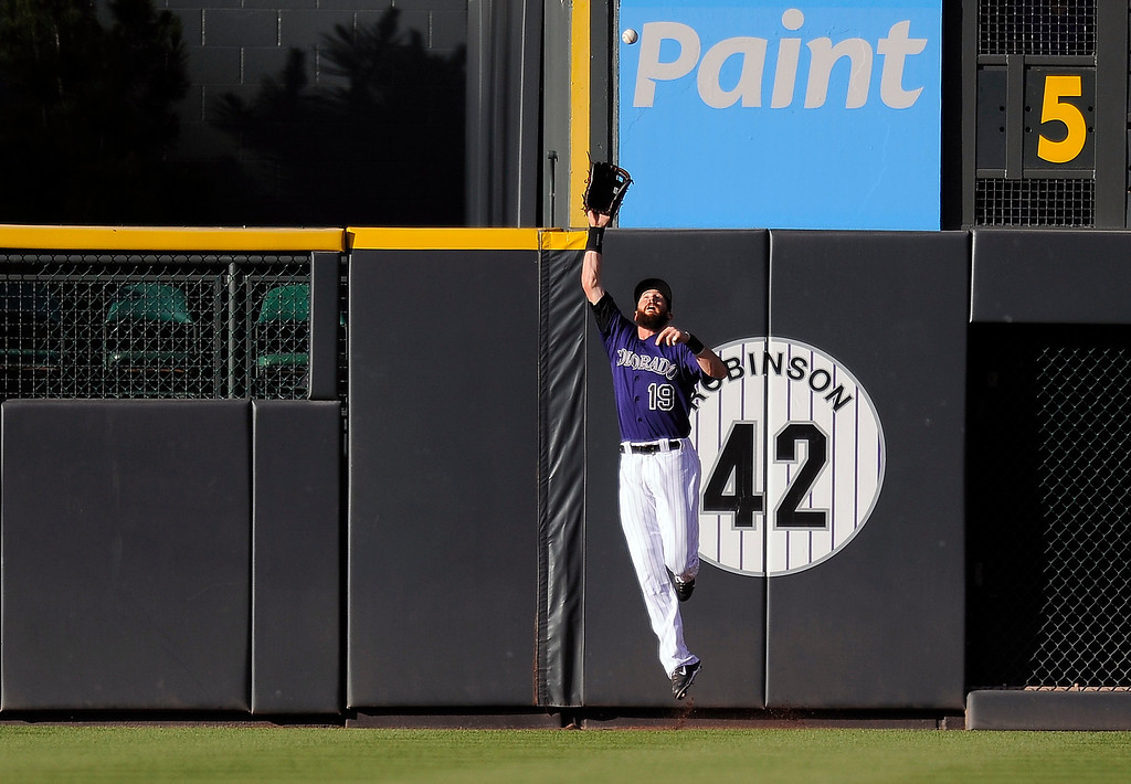 . Colorado Rockies center fielder Charlie Blackmon makes a leaping catch on a fly ball by Atlanta Braves Freddie Freeman in the first inning of a baseball game on Monday, June 9, 2014, in Denver. (AP Photo/Chris Schneider)