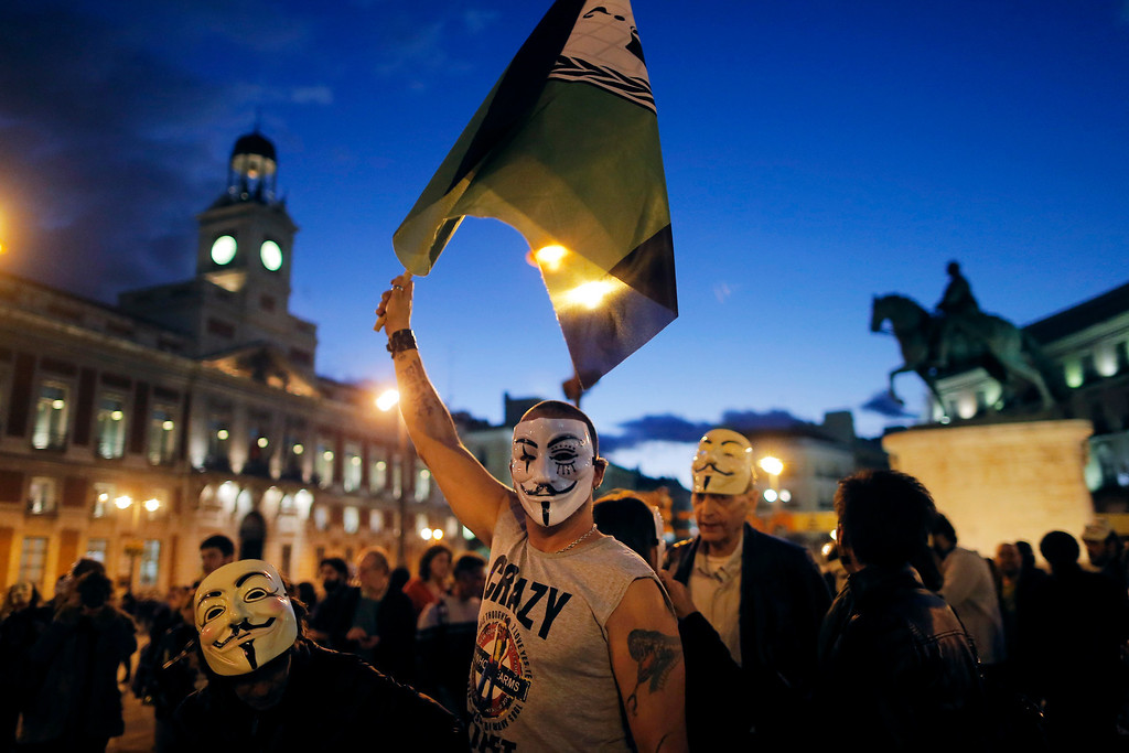 . A Spanish activist wearing a mask waves a anonymous flag during a protest against corrupt governments and corporations, in support of the anonymous activist movement, at the Sol square, in Madrid, Spain, Tuesday, Nov 5, 2013, as part of a Million Mask March of similar rallies around the world. (AP Photo/Andres Kudacki)