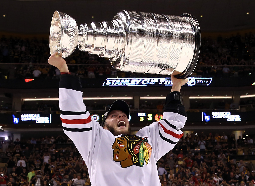 . Jonathan Toews #19 of the Chicago Blackhawks hoist the Stanley Cup Trophy after defeating the Boston Bruins in Game Six of the 2013 NHL Stanley Cup Final at TD Garden on June 24, 2013 in Boston, Massachusetts. The Chicago Blackhawks defeated the Boston Bruins 3-2.  (Photo by Bruce Bennett/Getty Images)