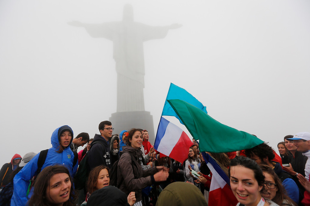 . Youth from France participating in World Youth Day sing songs below Christ the Redeemer statue in Rio de Janeiro, Brazil, Tuesday, July 23, 2013. The pope is here on a seven-day visit meant to fan the fervor of the faithful around the globe.  (AP Photo/Jorge Saenz)