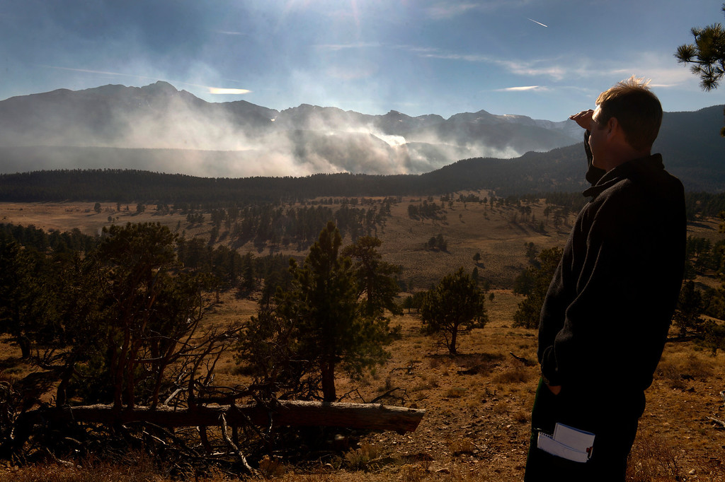 . Jake Brollier, Public Information Officer on the Fern Lake Fire, looks at the fire from the main road inside of the park. Officials are worried about winds kicking up later in the afternoon on December 2, 2012. The Fern Lake Fire, which has been burning in Rocky Mountain National Park since October, kicked up yesterday and forced the evacuation of hundreds of homes east of the fire. Helen H. Richardson, The Denver Post