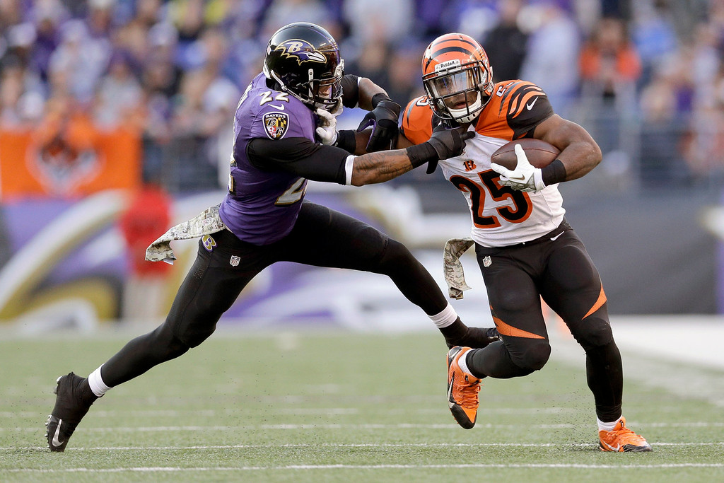 . Baltimore Ravens cornerback Jimmy Smith grabs Cincinnati Bengals running back Gio Bernard during the second half of a NFL football game in Baltimore, Sunday, Nov. 10, 2013. (AP Photo/Patrick Semansky)