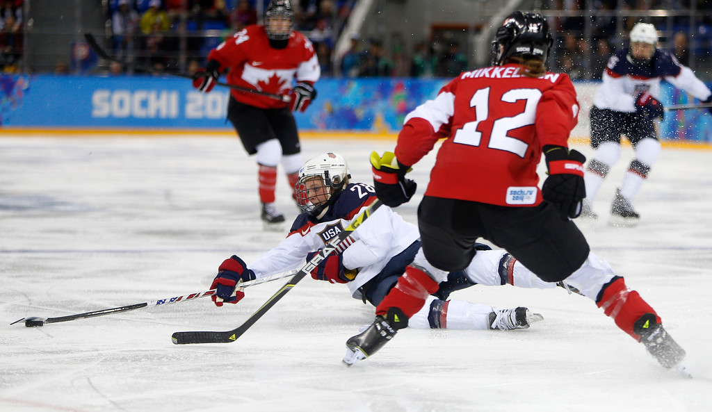 . USA\'s Amanda Kessel (28) loses her balance against Canada\'s Meaghan Mikkelson (12) in the second period for their preliminary round at the Shayba Arena for the 2014 Winter Olympics in Sochi, Russia on Wednesday, Feb. 12, 2014.  (Nhat V. Meyer/Bay Area News Group)