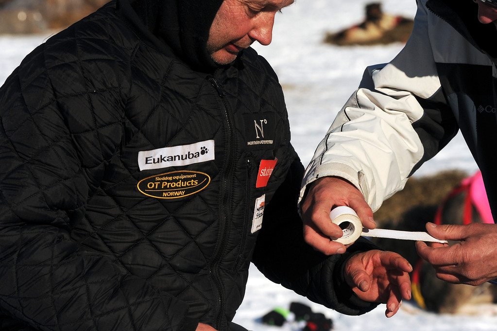 . In this March 3, 2014 photo, Ralph Johannessen gets his finger taped up at the Rainy Pass checkpoint during the 2014 Iditarod Trail Sled Dog Race near Puntilla Lake, Alaska. Johannessen had earlier cut the finger opening a can. (AP Photo/The Anchorage Daily News, Bob Hallinen)