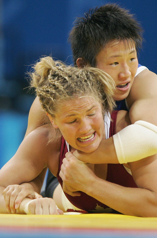 . Chinese female wristlers Xu Wang (blue) fights with Canadian Chris Nordhagen during a 72Kg female wrestling elimination pool, 22 August 2004, in the 2004 Olympic Games at the Ano Liossia stadiun in Athens, Greece. China won the match in the first ever women\'s wrestling Olympic Games. ANTONIO SCORZA/AFP/Getty Images