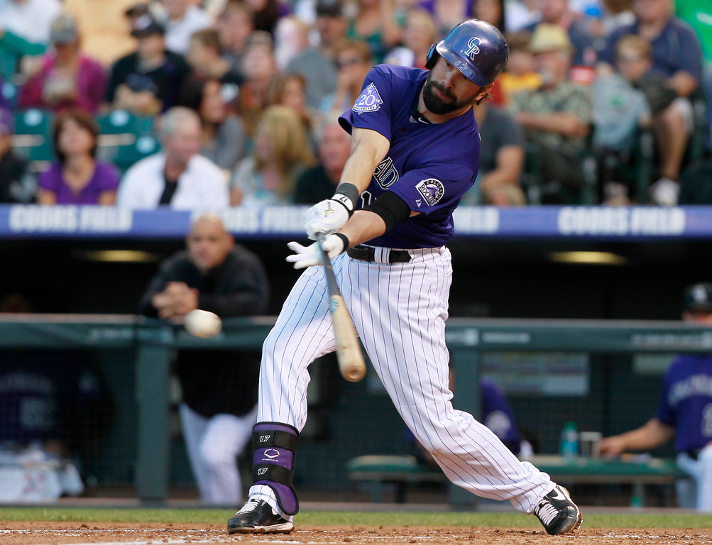 . Colorado Rockies\' Todd Helton lines out against the Arizona Diamondbacks in the first inning of a baseball game in Denver on Saturday, Sept. 21, 2013. (AP Photo/David Zalubowski)