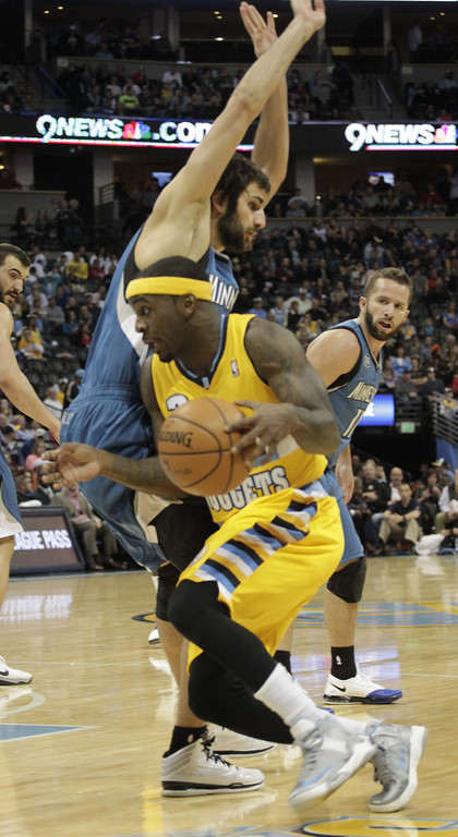 . Denver Nuggets guard Ty Lawson (3) collides with Minnesota Timberwolves guard Ricky Rubio, top, during the first quarter of an NBA basketball game in Denver, Friday, Nov. 15, 2013. (AP Photo/Joe Mahoney)