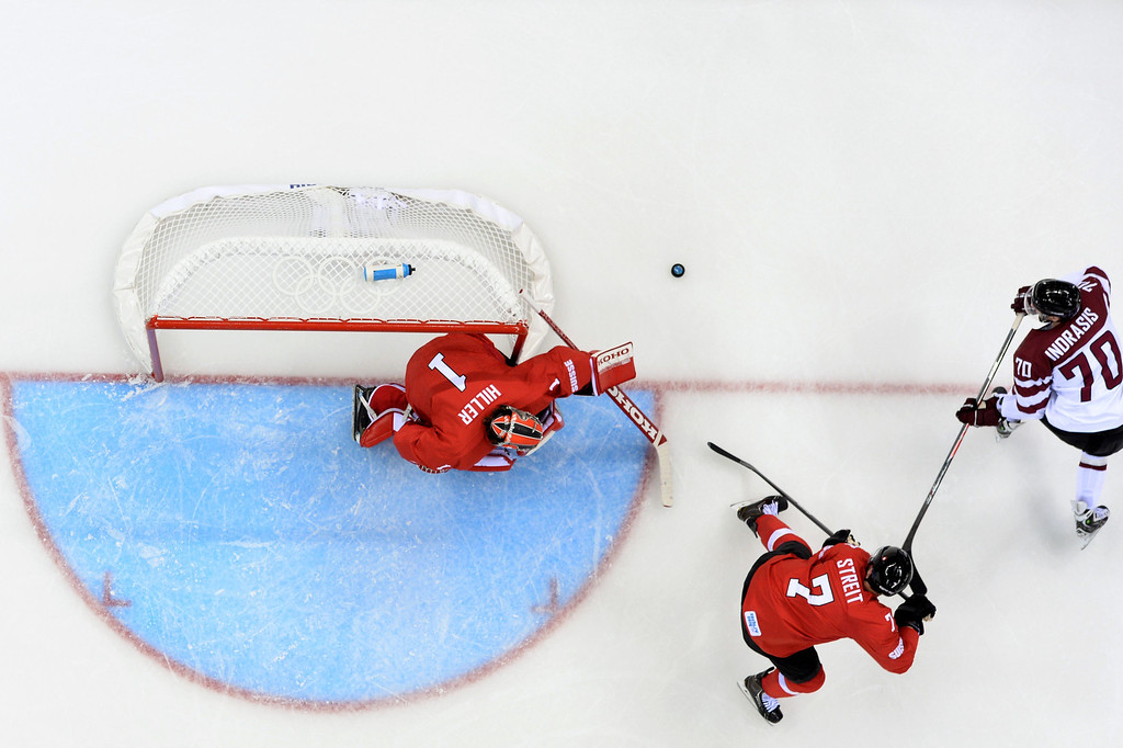 . (LtoR) Switzerland\'s goalkeeper Jonas Hiller and Switzerland\'s Mark Streit and Latvia\'s Miks Indrasis vie in the Men\'s Ice Hockey Group C match Latvia vs Switzerland at the Shayba Arena during the Sochi Winter Olympics on February 12, 2014 in Sochi.  ANDREJ ISAKOVIC/AFP/Getty Images