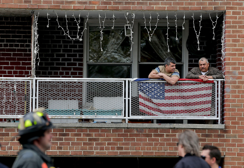 . Residents of an apartment building at 60th Street and Broadway in Queens borough of New York,  watch as emergency crews evacuate passengers from a subway tunnel after a train derailed, Friday, May 2, 2014. The express F train was bound for Manhattan and Brooklyn when it derailed at 10:40 a.m. Dozens of firefighters and paramedics with stretchers converged on Broadway and 60th Street, where passengers calmly left the tunnel through the sidewalk opening. A few were treated on stretchers. (AP Photo/Julie Jacobson)