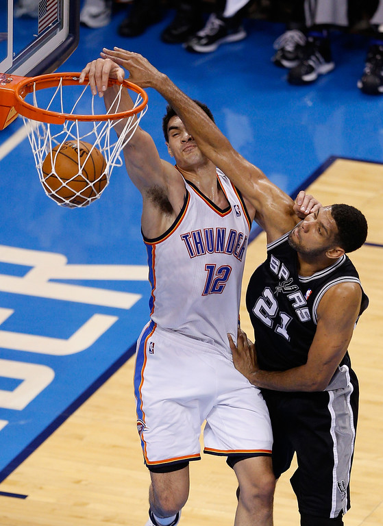 . OKLAHOMA CITY, OK - MAY 27:  Steven Adams #12 of the Oklahoma City Thunder drives to the basket against Tim Duncan #21 of the San Antonio Spurs in the first half during Game Four of the Western Conference Finals of the 2014 NBA Playoffs at Chesapeake Energy Arena on May 27, 2014 in Oklahoma City, Oklahoma. (Photo by Joe Robbins/Getty Images)