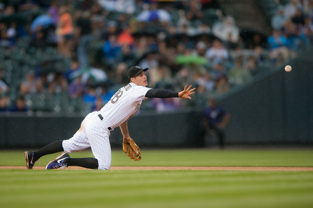 . Nolan Arenado #28 of the Colorado Rockies puts out a runner at second base from his knees after nearly making an acrobatic catch in the fifth inning of a game against the Pittsburgh Pirates at Coors Field on July 26, 2014 in Denver, Colorado.  (Photo by Dustin Bradford/Getty Images)